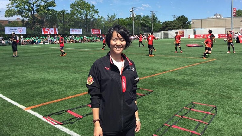 Sayako standing on the sidelines of a soccer field with a SO Soccer practice taking place in the background