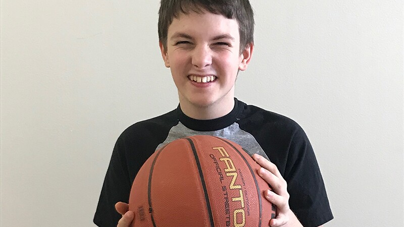 Jaden James smile and holding a basketball.