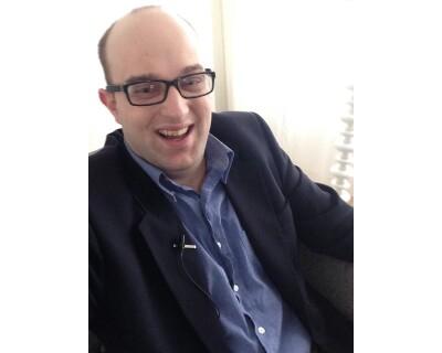 photo of Daniel Smrokowski sitting and smiling.