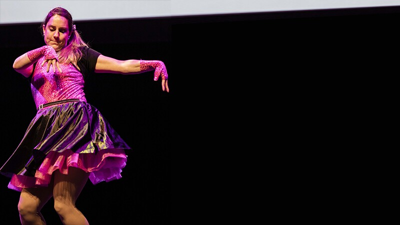 Girl dancing in pink and purple top and skirt on stage.