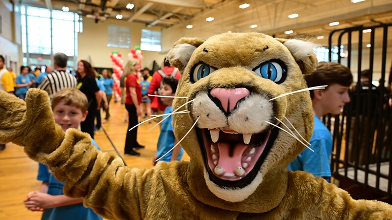 Tiger mascot posing for photo with athletes in the background.