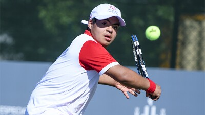 Young man swings his racket in a backhand to hit a tennis ball.
