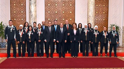 The Egyptian Unified Football team and the Egyptian President lined with 3 Egyptian flags on each side.