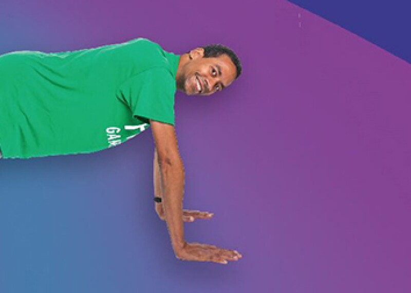 Athlete planking, he's in a green t-shirt and sneakers with gray shorts. The background is different shades of purple in an organic pattern.