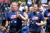 Bree running and holding the flame of hope with another runner.