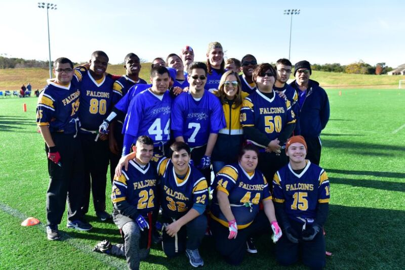 A Special Olympics coach smiles with her flag football team.