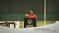 Loretta Claibourne on stage behind a podium speaking.