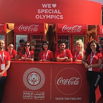Coca Cola representatives standing at the Coca Cola booth during World Games Abu Dhabi 2019
