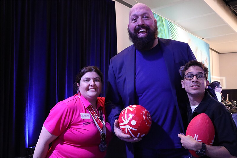 Global Ambassador Big Show standing between athletes Michelle Canazaro and Sebastian Cespedes.