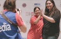 Athlete and Special Olympics representative give one another a high-five as a media photographer takes their picture.