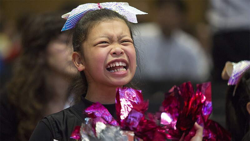 Young female cheerleader and athlete smiling and exuding joy.