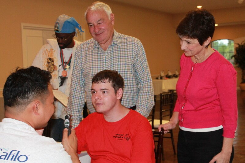 Tom Golisano and Ann Costello standing behind a seated Special Olympics athlete observe an eye screening in progress.