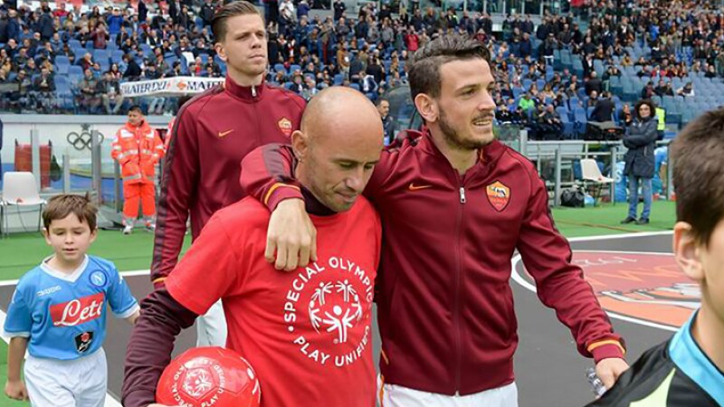 Pro footballer with his arm around a unified palyer that is carrying a football onto the field. The unified player is wearing a red t-shirt that says Special Olympics, Play Unified.