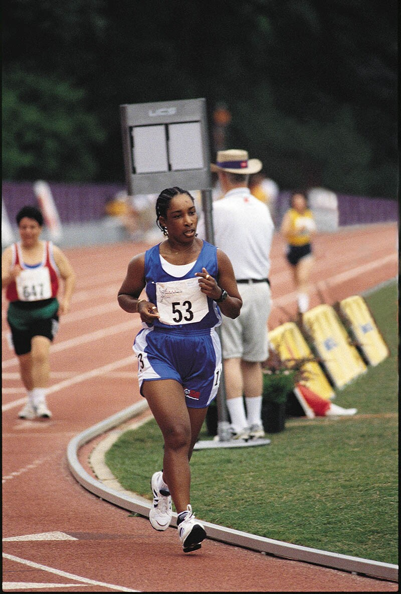 Loretta Claiborne of York, Pa., running on a track in blue shorts and tank top; her bib reads 53.