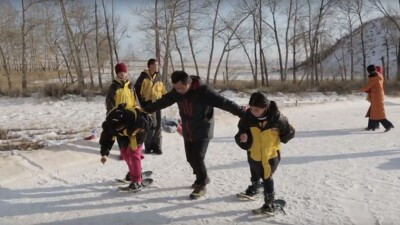 An adult is assisting younger athletes run in the snow.