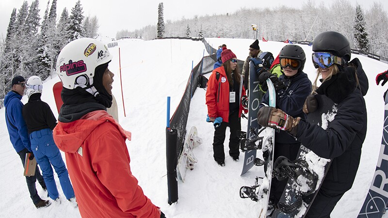Latrice talking to Hanna Teter and other snowboarders on the slopes.