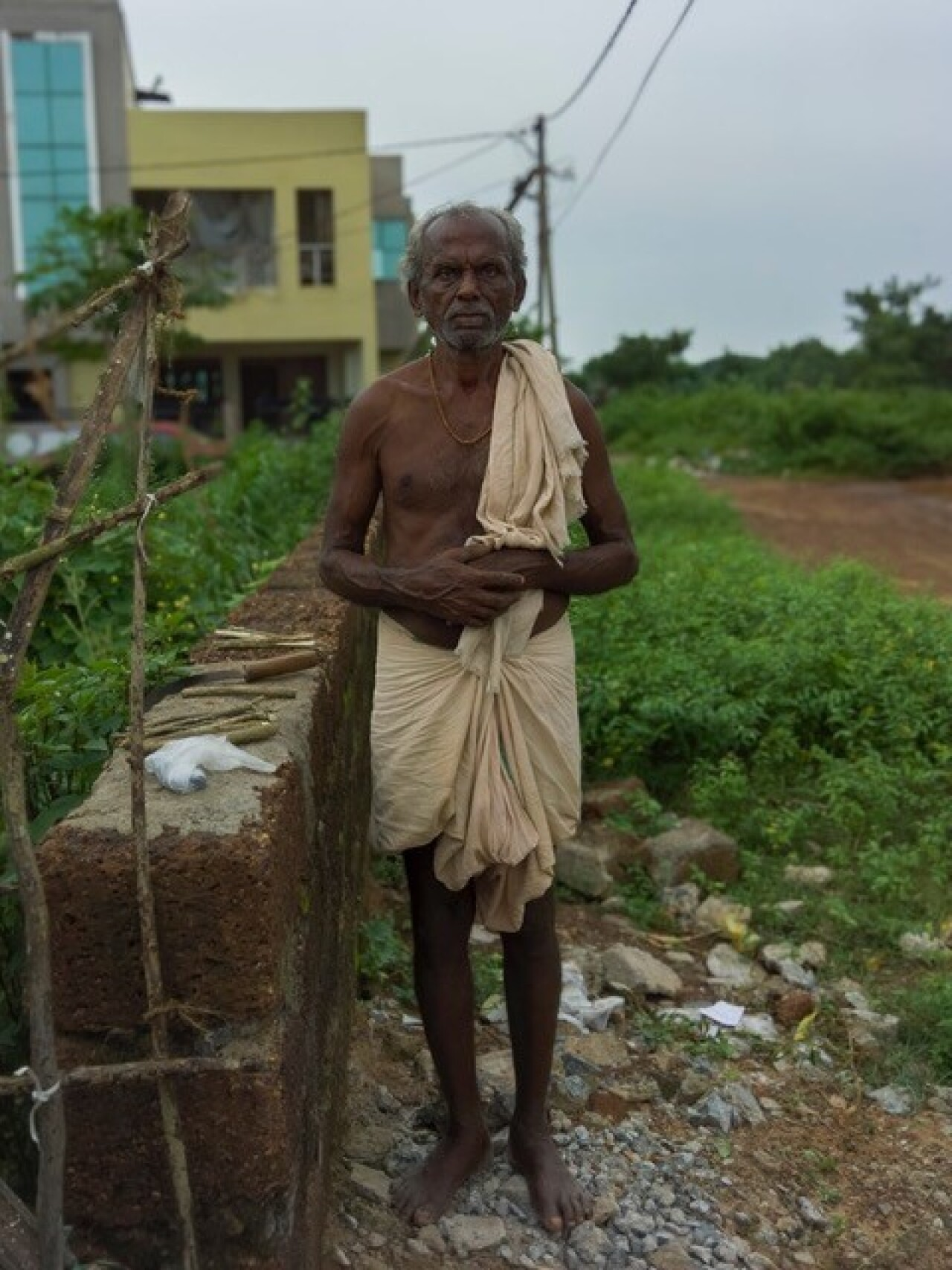 An older man in a dhoti with one hand on top of another looking at the camera standing on a small lading of rocks between a brick wall and open grass, dirt, and shrubbery laden field. In the background are small two level homes.