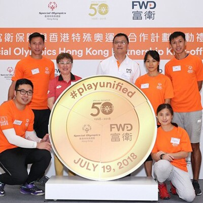 Special Olympics Hong Kong athletes and representatives standing behind and beside a round visual that reads: #PlayUnified.