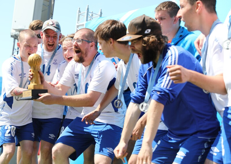 A group of men in blue shorts and white t-shirts stand together around one man who is holding a trophy. They have their mouths open as if shouting or cheering.