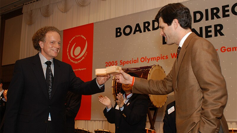Bruce Pasternack and Timothy Shriver hold up wooden boxes in an event room.