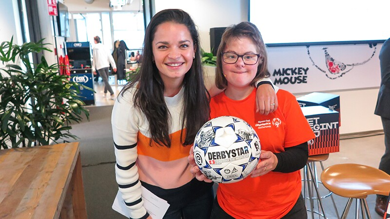 Young woman with her arm around Lize's shoulder, Lize is holding and Derbyster football and both are smiling.