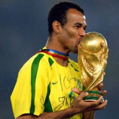 Cafu wearing his yellow and green jersey with a blue gold and red ribbon around his neck holding and kissing a gold trophy