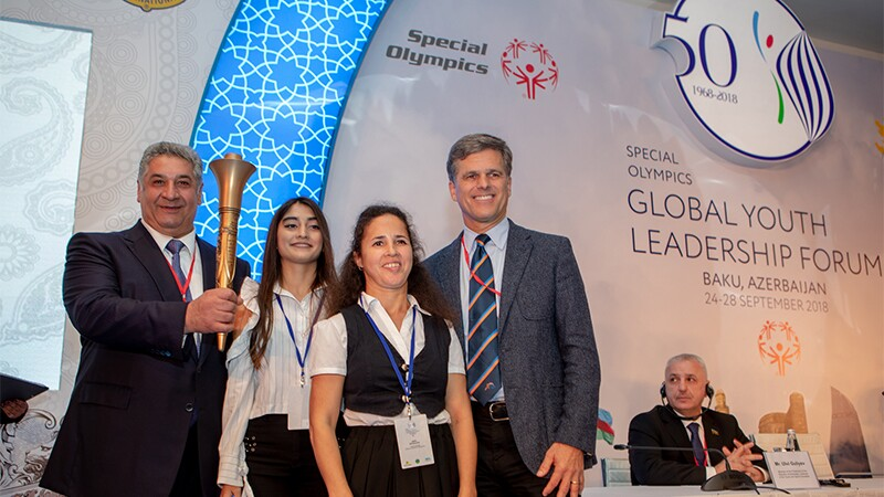 Special Olympics Chairman Dr Timothy Shriver (L) and the honorable Azad Rahimov, Minister of Youth and Sport of Azrbaijian together with Special Olympics athletes from Azerbaijan light the flame.