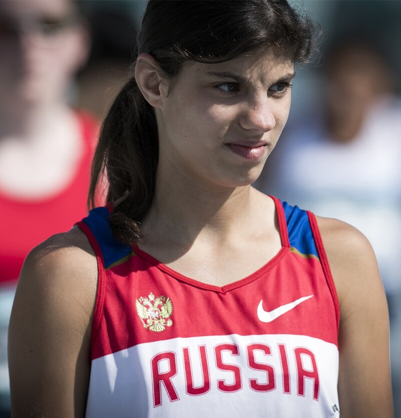 Tatiana Baranova, athlete leader from Special Olympics Russia standing on the field in an athletic tank-top that reads: Russia