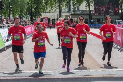Runners in red t-shirts running towards the camera across a finish line.