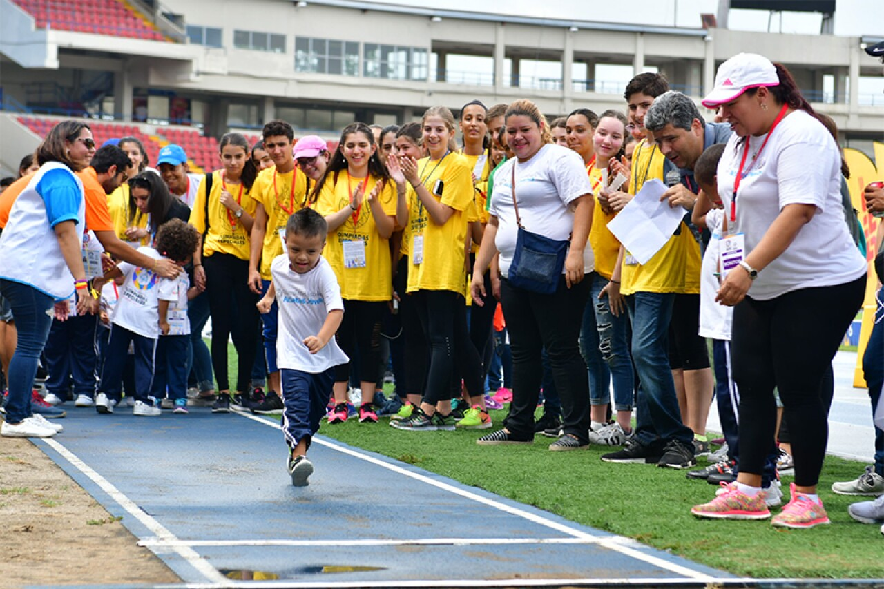 Young athlete runs while adults cheer him on.