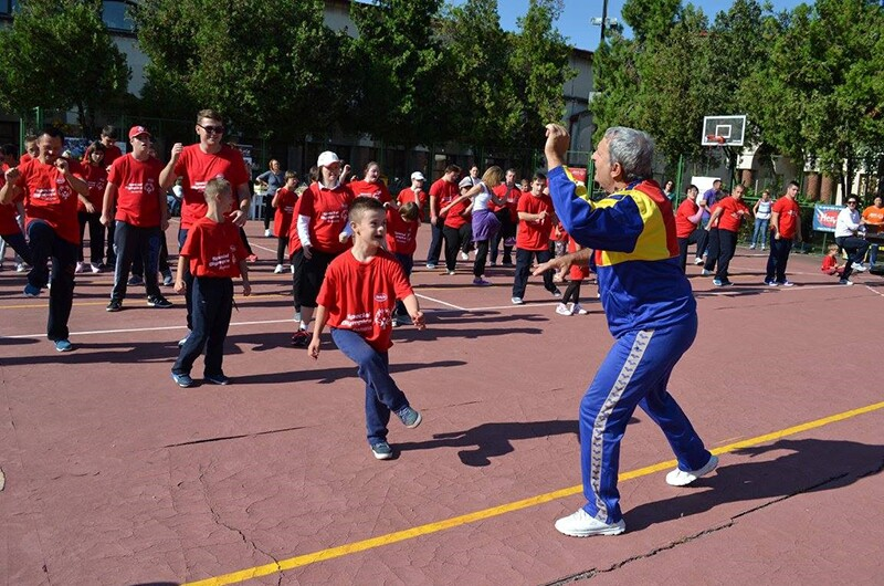 Coach and athletes on an outdoor basketball court; the coach is at the front wearing a a blue, red, and yellow jump suite coaching athletes and non athletes of all ages. Participants are wearing red So Fit t-shirts and dark pants.