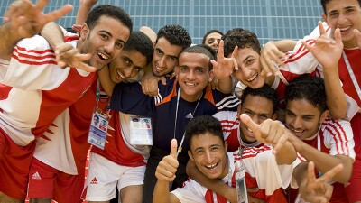 A group of athletes close together posing with thumbs up and the peace sign; athletes are wearing red and white Adidas football uniforms.