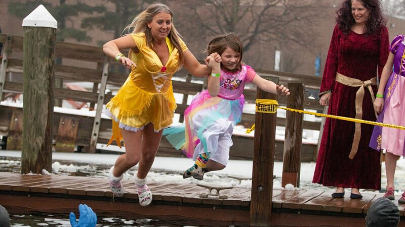Mother and daughter dressed as princesses holding hands and jumping into the water.