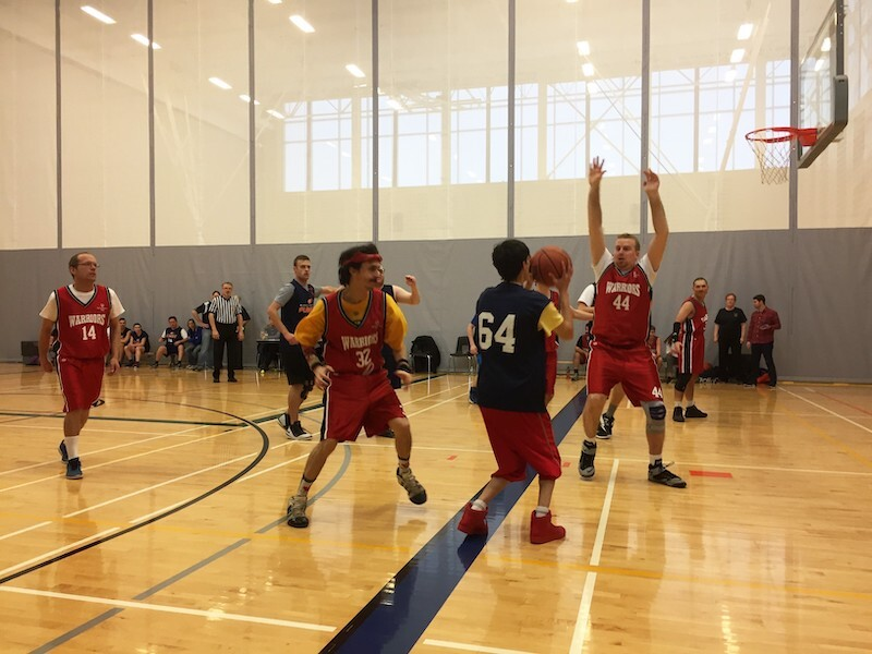 A group of Special Olympics athletes play basketball in a gym.