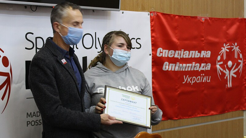 A young woman standing next to an older man handing her over a framed certificate.