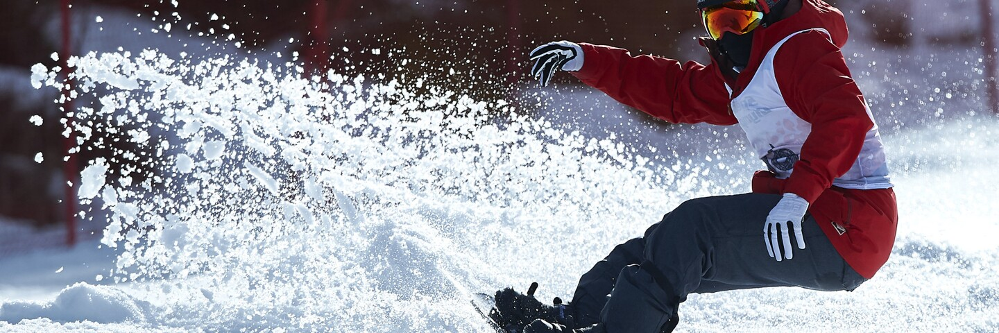 Snowboarder in a red ski jacket and gray ski pants performing moves in the snow.