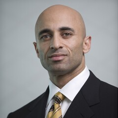 Ambassador Yousef Al Otaiba in a dark suite, white shirt, and yellow,gold, and black striped tie.