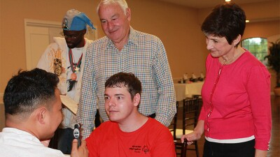 Ann Costello and Tom Golisano watch an athlete receive an eye exam.