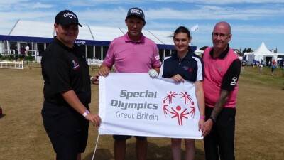 Four people standing out together holding a banner that reads: Special Olympics Great Britain.