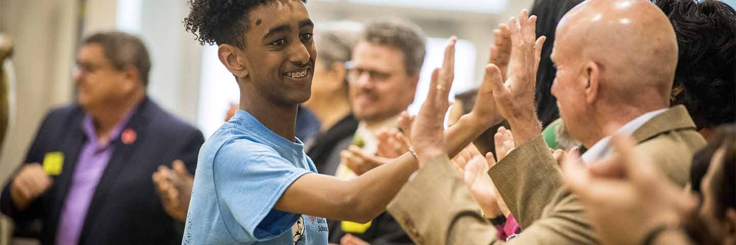Student giving high-5s to adults that are standing in a line.