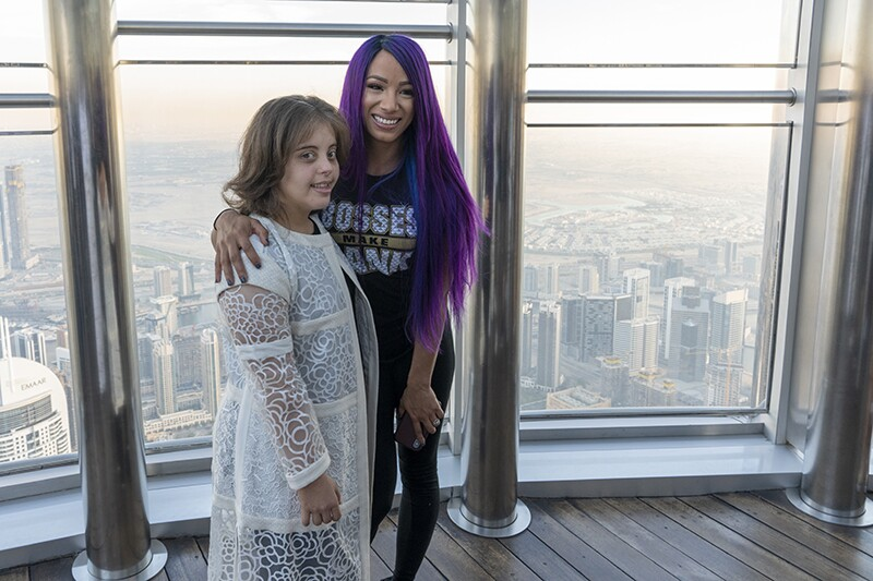 WWE Superstar Sasha Banks and Team UAE athlete Chaica Sultan Al Qasimi pose at the Burj Khalifa. In the background is the city of Abu Dhabi.