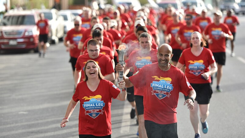 Sherrie and a law enforcement officer carries the torch and leads the Final Leg run group down a road.