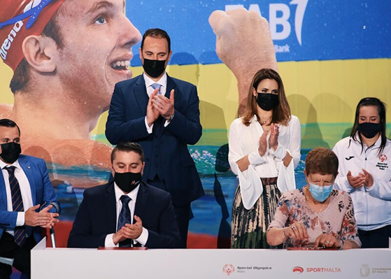 Two people sit behind a desk looking at a document in with a group of four people behind them clapping. Everyone is wearing a face mask.