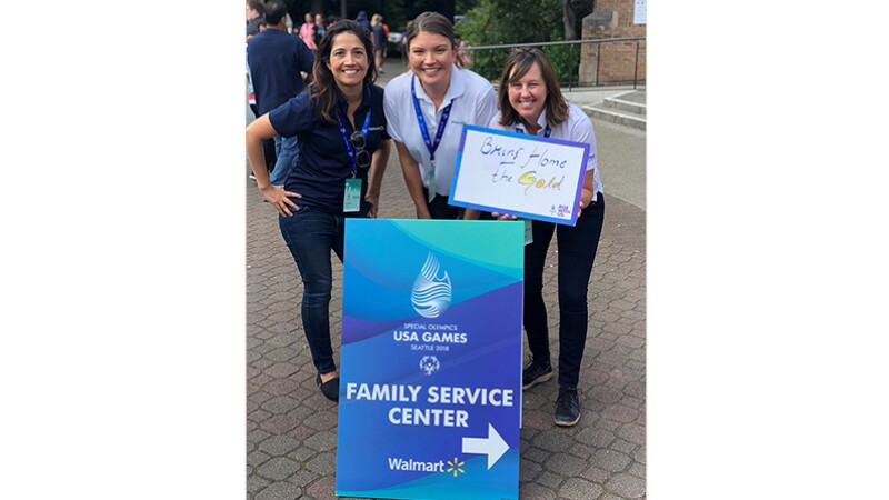 Three Walmart and Special Olympics representatives standing behind a sign that reads: Special Olympics USA Games Seattle 2018 Family Service Center; Walmart.