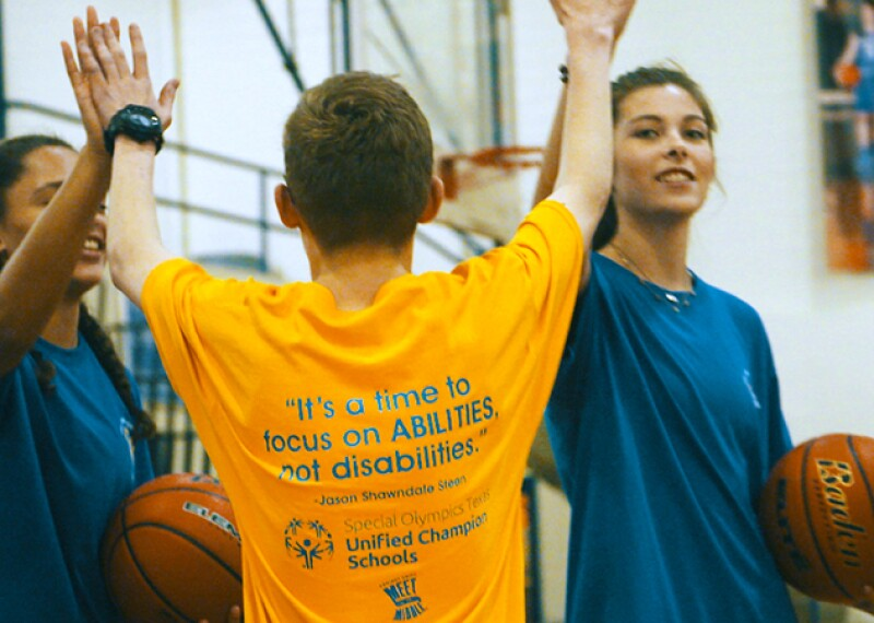 One student in yellow gives another two students in blue a high five in a gymnasium. The two students in blue are holding a basketball each.