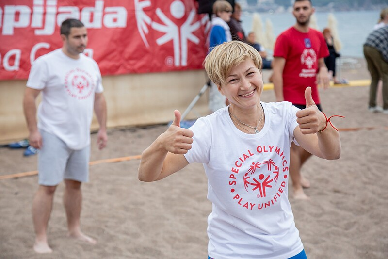 Ekaterina Sazonova, wearing a Special Olympics Play Unified white t-shirt, takes part in Unified (beach) Volleyball as the Special Olympics Europe Eurasia Leadership Conference draws to a close. Erika is giving a double thumbs up and is on the beach with two other athletes