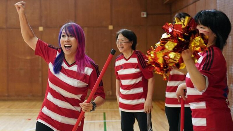 Young girl with purple and pink hair holds a floor hockey stick and cheers as athletes and parents also cheer and look on.