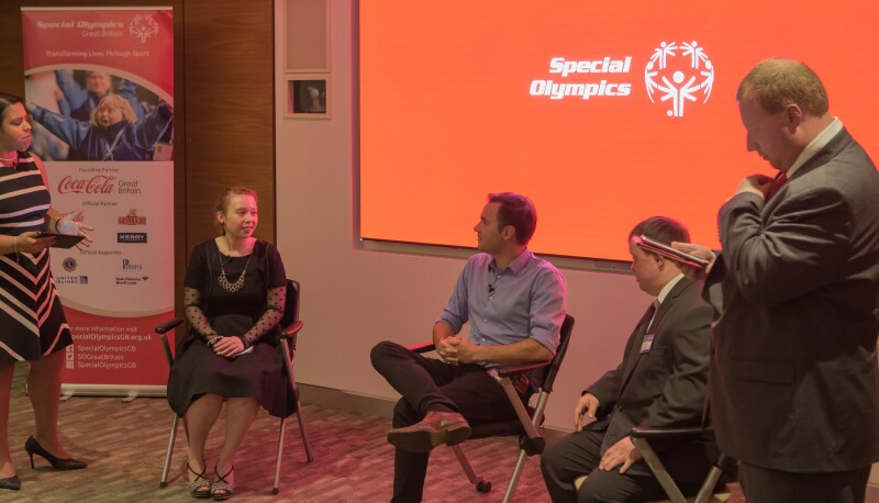 Three people sit in front of a screen branded with the Special Olympics logo. A female and male stand at either side of them.