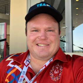 Ben Haack smiling for a photo sitting outside at a sports venue.