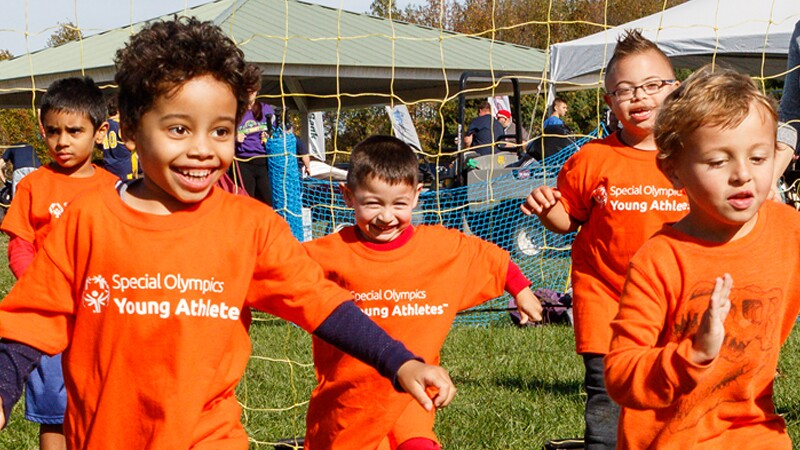 Young children on a field all wearing orange Special Olympics Young Athlete t-shirts.